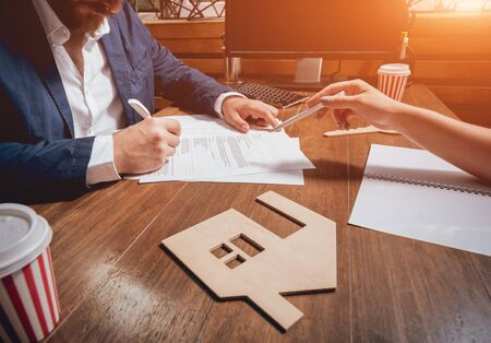 Man sign a home insurance policy on home loans. Estate agent with customer