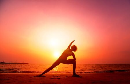 Mooie jonge vrouw beoefent yoga op het strand. Oefening in de vroege ochtend. Zonsopkomst. Palmen achtergrond