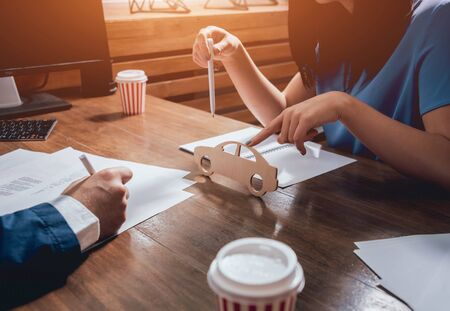Man signing a car insurance policy, the agent is holding the wooden car model.