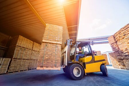 Forklift loader load lumber into a dry kiln. Wood drying in containers. Industrial concept Stock Photo