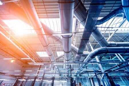 Klimatisierung von Gebäuden. Hintergrund der Lüftungsrohre. Verlegung von Engineering-Netzwerken. Industrieller Hintergrund