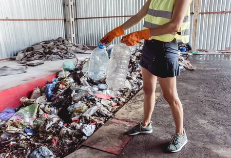 Woman-volunteer sorting trash at modern recycling plant. Separate garbage collection. Trash sorting. Background 版權商用圖片