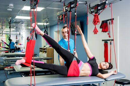 Physiotherapy. Suspension training therapy. Young woman doing fitness traction Stock fotó