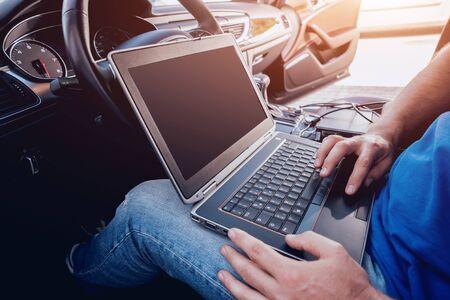 Mechanic man with laptop making car diagnostics at auto service. Background Stock Photo