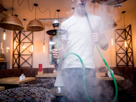 Cooking hookah in the bar. Young man with hookah in restaurant Stock Photo