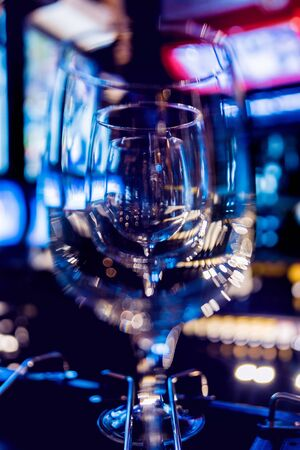 Wine and martini glasses in shelf above a bar rack in restaurant. Empty clean glasses in bar. Background