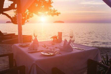 Wine glasses on the table of bar. Sunset over the sea. Background Reklamní fotografie