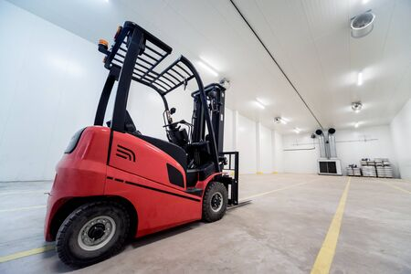 Forklift in a large industrial freezer warehouse.