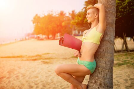 Beautiful young woman practic yoga at the beach. Early morning exercise Zdjęcie Seryjne