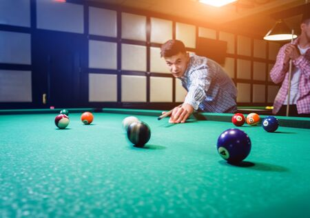 Young man trying to hit the ball in billiard.