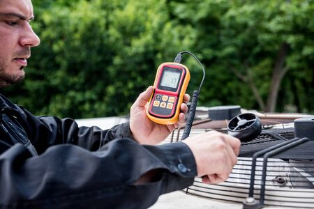 Technician use hand-held anemometer measuring air flowing measurement Stock Photo