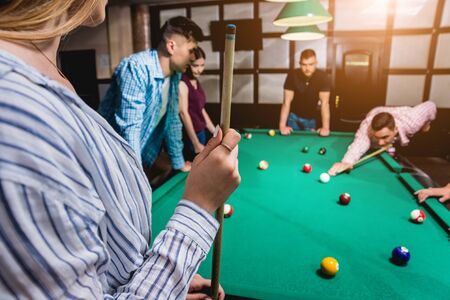 Group of young cheerful friends playing billiards. Funny time after work