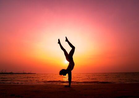 Schönes praktizierendes Yoga der jungen Frau am Strand. Übung am frühen Morgen. Sonnenaufgang. Palmen-Hintergrund