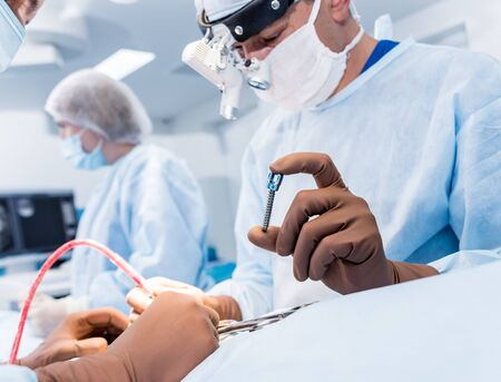 Spinal surgery. Surgeon show polyaxial screw in operating room with surgery equipment. Laminectomy. Spine fixation systems. Medical background