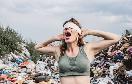 A blindfolded female volunteer screams from powerlessness in a dump of plastic rubbish. Bushes and sky in the background. Earth day and ecology. Concept