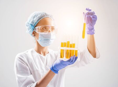 Scientist pouring organic oil. Beauty and cosmetics sciences. Laboratory equipment. White background