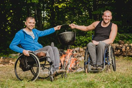 Two disabled men resting in a campsite with friends. Wheelchair in the forest Zdjęcie Seryjne