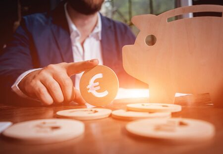 Businessman holds a coin near wooden piggy. Money box. Collecting money with earning bank. Deposit ideas. Business concept