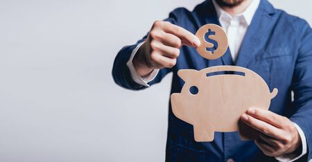 Businessman holds a coin under wooden piggy. Money box. Collecting money with earning bank. Deposit ideas. Business concept