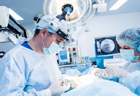 Spinal surgery. Group of surgeons in operating room with surgery equipment. Laminectomy. Modern medical background