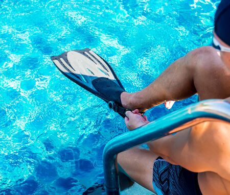 Young athletic man wearing flippers by the pool. Active sport Reklamní fotografie - 140550876