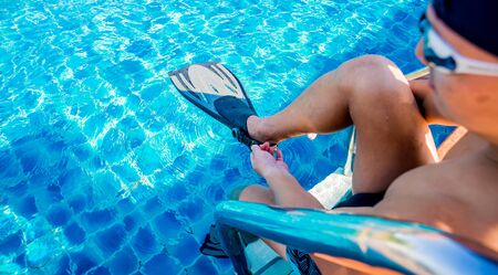 Young athletic man wearing flippers by the pool. Active sport Reklamní fotografie
