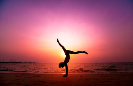 Beautiful young woman practic yoga at the beach. Early morning exercise. Sunrise. Palms background
