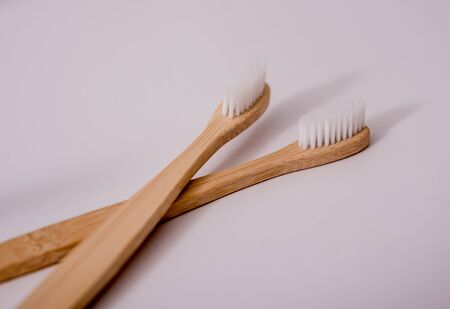 Bamboo toothbrushes, washcloths, cups and plates on the white table in kitchen. Zdjęcie Seryjne
