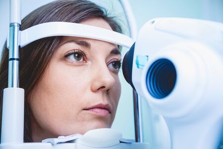 Doctor examining womans eyes with a measurement machine. Stock Photo