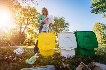 Volunteer girl sorts garbage in the street of the park. Concept of recycling. Archivio Fotografico