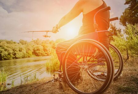 Handicapped man fishing at a lake. Wheelchair camping. Summertime background