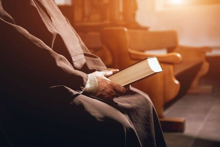 A monk in robes with holy bible in their hands praying in the church Standard-Bild
