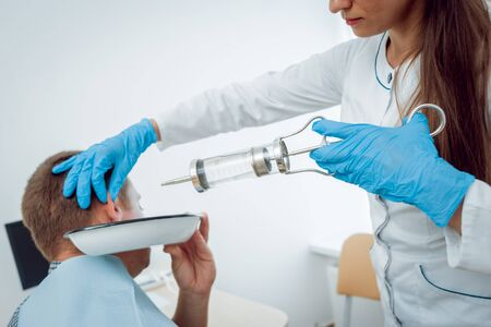 Medical ear washing with water in big syringe. Ear irrigation and earwax removal