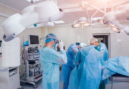 Doctor in a surgical room with virtual reality glasses on the background of the real operation. Modern technologies