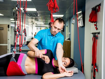 Physiotherapy. Suspension training therapy. Young woman doing fitness traction Reklamní fotografie
