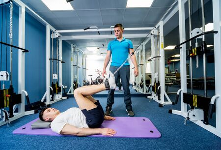 Rehabilitation therapy. Young man doing exercises on mat