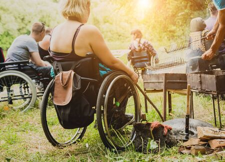 Disabled man resting in a campsite with friends. Wheelchair in the forest on the background of bonfire. Barbeque. Camping. Summertime