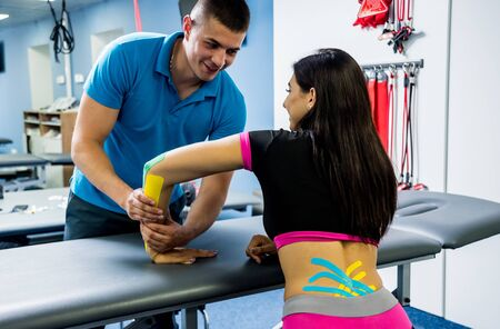 Kinesiotaping. Physical therapist applying tape to young beautiful womans spine Reklamní fotografie