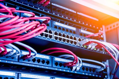Network switch and ethernet cables in red and white colors. Data Center. Background