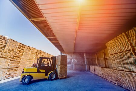 Forklift loader load lumber into a dry kiln. Wood drying in containers. Industrial concept