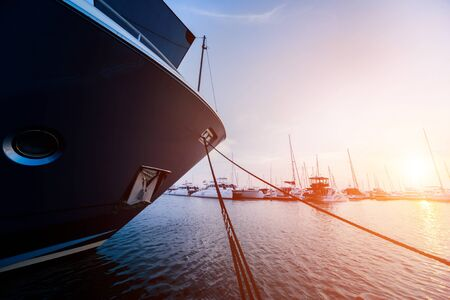 Beautiful view of marina and harbor with yachts and motorboats. Sunset at the ocean. Background