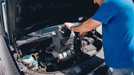 Accumulator charging. Hands and terminal. Car and repair. Service station.