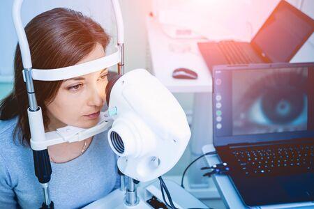 Doctor examining womans eyes with a measurement machine. Zdjęcie Seryjne