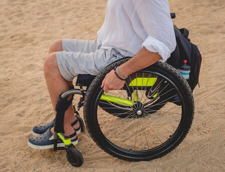 Disabled man in a wheelchair on the beach. Concept background