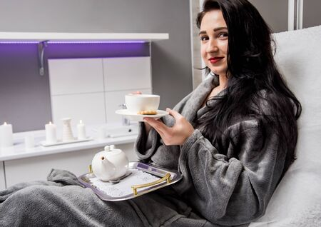Young woman drinking herbal tea after spa procedures.