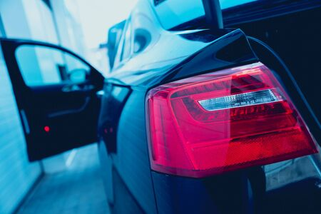 Back view of black car. City background.