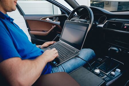 Mechanic man with laptop making car diagnostics at auto service. Background