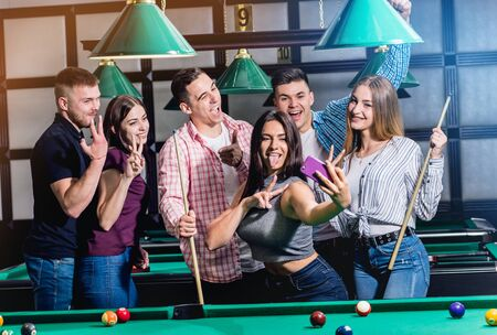 A group of friends makes a selfie at the pool table. 版權商用圖片