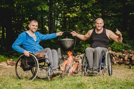 Two disabled men resting in a campsite with friends. Wheelchair in the forest 版權商用圖片