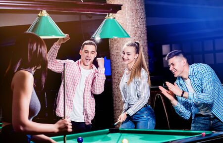 Group of young cheerful friends playing billiards. 版權商用圖片 - 142086988